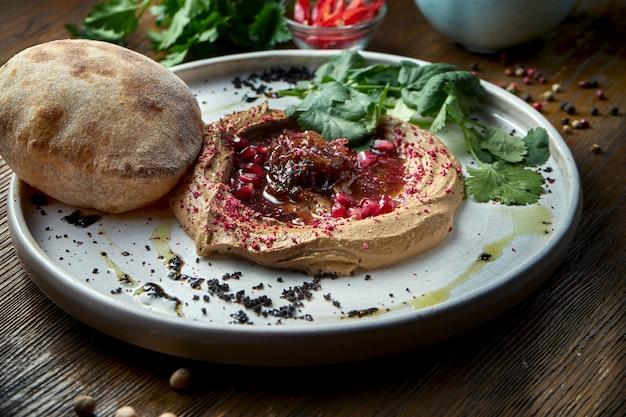 食欲をそそるフランス料理-タマネギジャムとピタパンを添えたチキンパテを木製のテーブルの白い皿に盛り付けました。クローズアップビュー