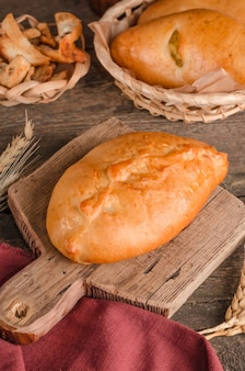 Appetizing fresh culinary pastry filled patty on wooden cutting board and background