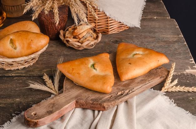 食欲をそそる新鮮な料理のペストリー-木製の背景にさまざまな詰め物のパイ
