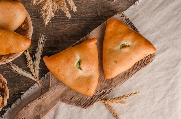 Appetizing fresh culinary pastry  pies with different fillings on a wooden background