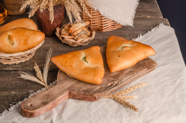 Appetizing fresh culinary pastry - pies with different fillings on a wooden background
