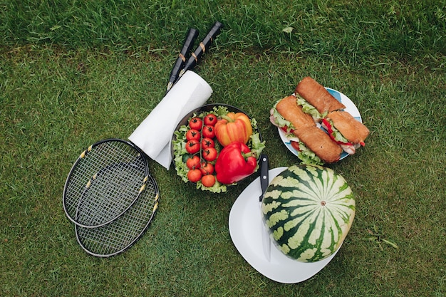Appetizing fresh food ready outdoor summer picnic on green grass top view