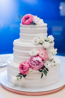 Appetizing fresh pastry cake covered by white cream icing and decorate sweet flower serving on table