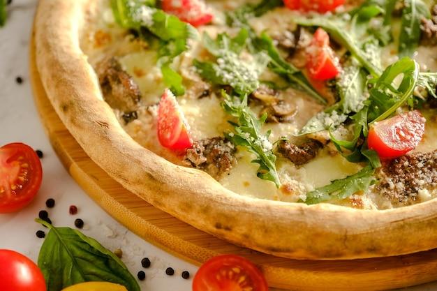 食欲をそそる新鮮なピザがテーブルの上にあります。イタリア料理店の料理。ピザを調理します。ピザの材料。友達と夕食。