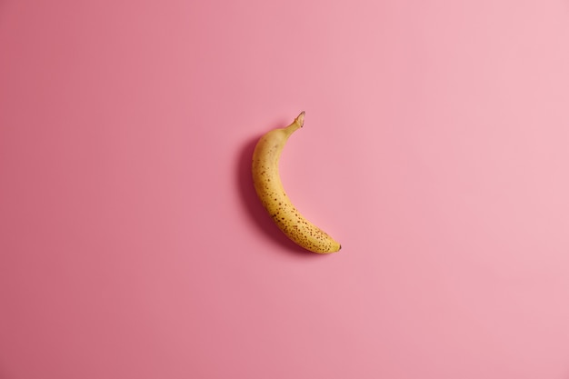 Аппетитный свежий весь желтый банан, изолированные на розовом фоне. вкусные неочищенные фрукты на завтрак. горизонтальный снимок. спелые фрукты, содержащие много калорий и витаминов. концепция чистой еды.