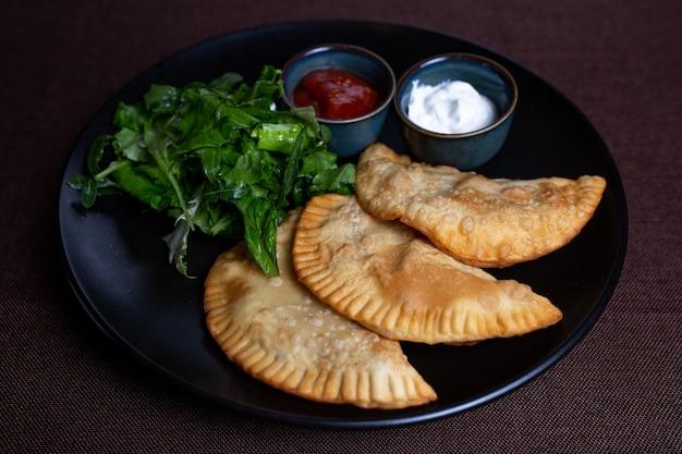 채소와 함께 검은 접시에 식욕을 돋우는 튀김 chebureks.