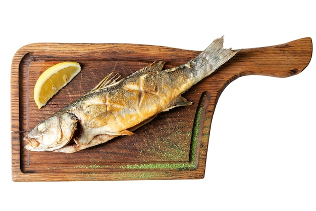Appetizing fried fish with lemon on a wooden board
