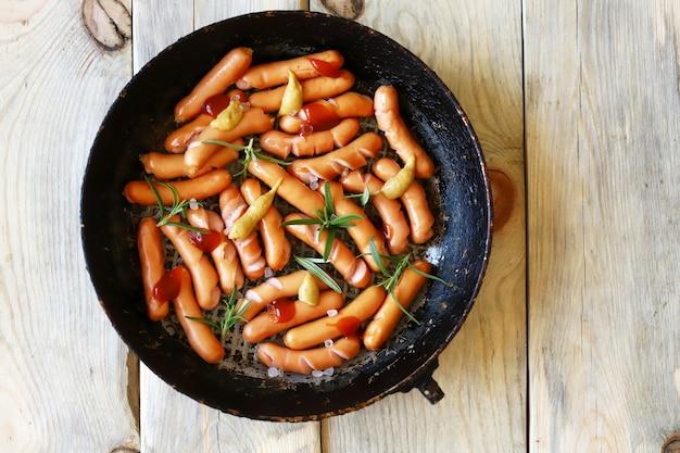 냄비에 식욕을 돋우는 튀긴 미니 소시지. 유기농 소시지. 소박한 스타일.