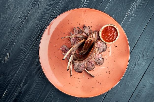 Аппетитно обжаренная на гриле баранина, подается в тарелке с красным соусом на темной поверхности. барбекю