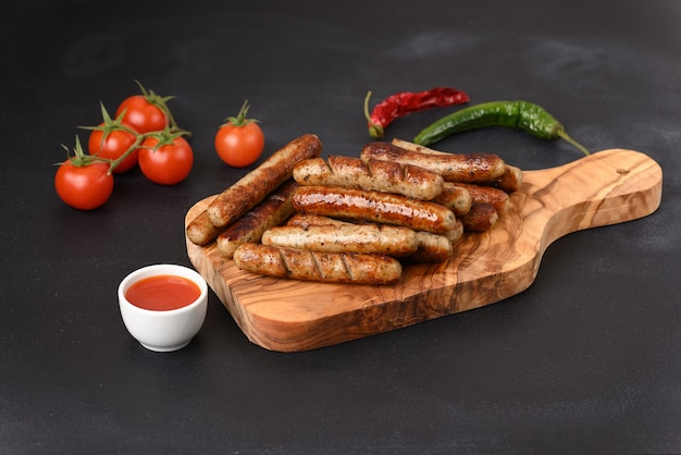 Аппетитные жареные колбаски с острым соусом чили на темном фоне.