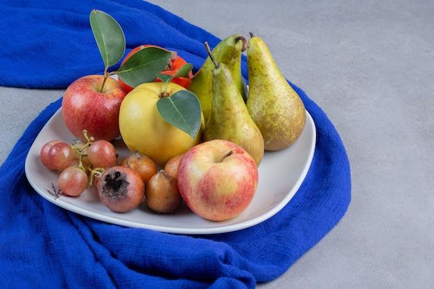 大理石の背景の青いテーブルクロスに食欲をそそるフルーツの品揃えの盛り合わせ。