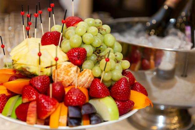 お祝いのテーブルの上の食欲をそそるフルーツプレート。ビジネスミーティング、イベント、お祝いのケータリング。