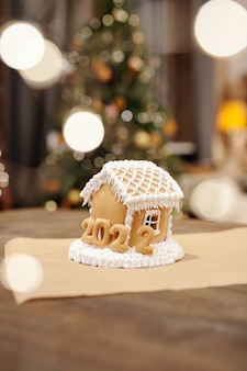 Appetizing gingerbread house decorated with whipped cream and baked numbers of the next year
