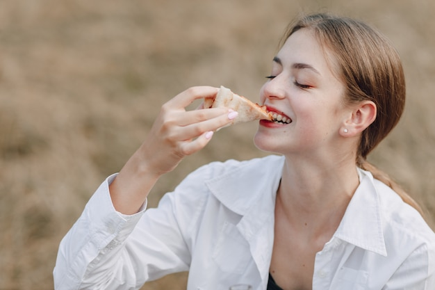 Appetizing girl eating pizza