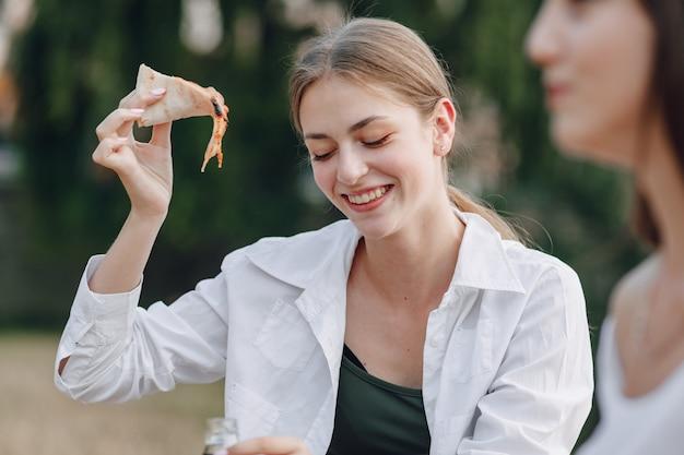 Appetizing girl eating pizza