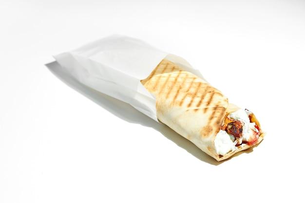 Аппетитные греческие гироскопы с сувлаки, помидорами, огурцами, картофелем фри в лаваше с йогуртом. оберточная бумага. уличная еда, жесткий свет. белая поверхность