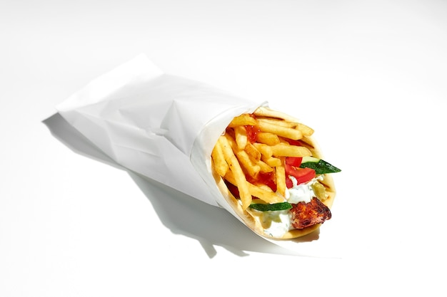 Appetizing greek gyros with souvlaki, tomatoes, cucumbers, fries in a pita with yogurt. wrapping paper. street food, hard light. white surface