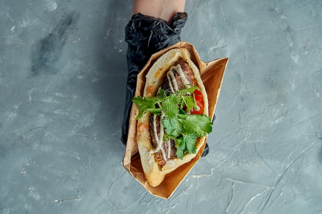 Appetizing greek pita sandwich with kebab, cilantro, cherry tomatoes and white sauce