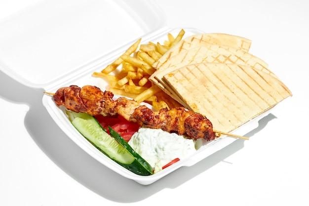 Appetizing greek souvlaki with cucumbers, fries, pita, yoghurt in a plastic lunch box. street food, hard light. white surface