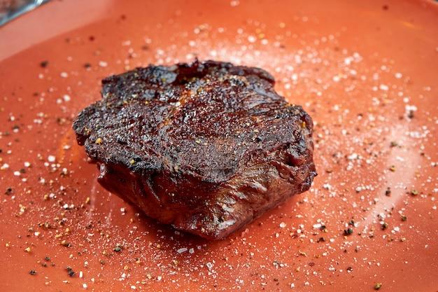 食欲をそそる熟成リブアイビーフステーキのグリルを木製の木製テーブルのプレートでお召し上がりいただけます