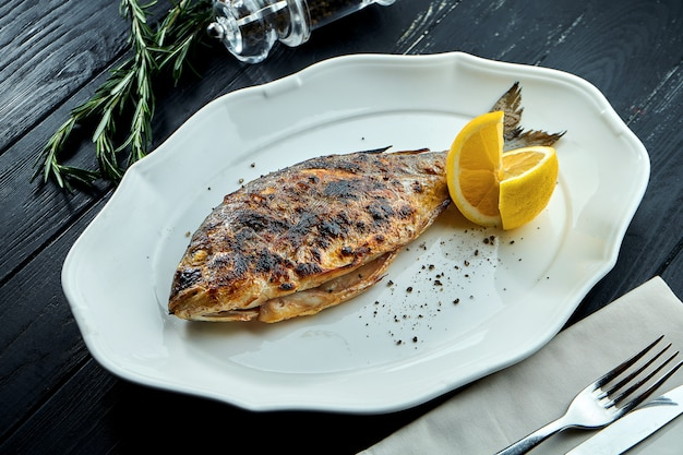 Appetizing grilled dorado on charcoal with lemon, served in a white plate on a dark wood background.