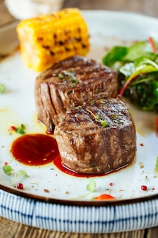 Appetizing grilled filet mignon steak with corn