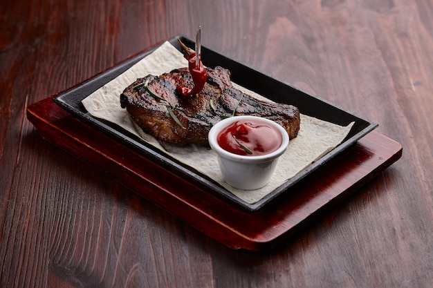 Appetizing grilled meat dishes with sauce on a dark wooden table.