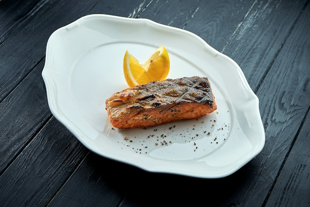 Appetizing grilled salmon steak on charcoal with lemon, served in a white plate on a dark wooden background. bbq seafood