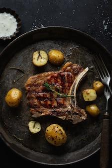 Аппетитный стейк на гриле на старой сковороде с картофелем на темном фоне. вид сверху.