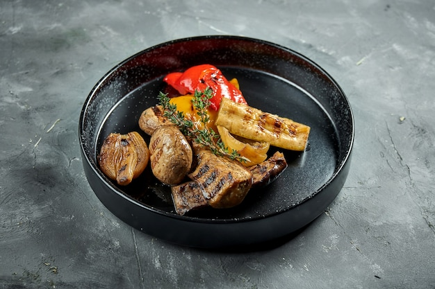 Appetizing grilled vegetables served in a black plate on a gray surface