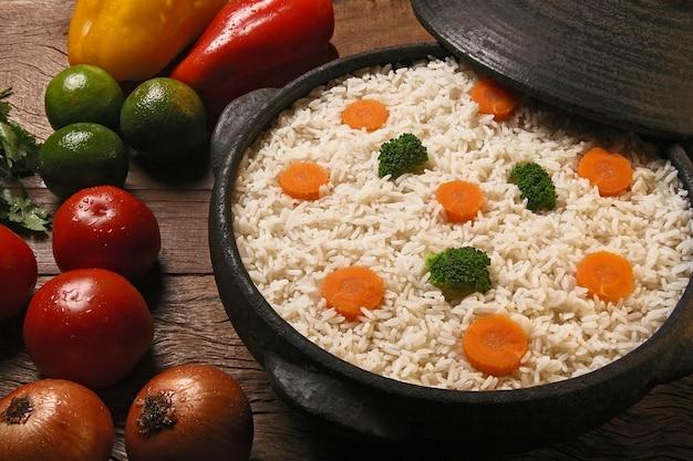 Аппетитный здоровый рис с овощами в белой тарелке на деревянной поверхности