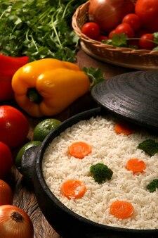 나무 테이블에 흰 접시에 야채와 함께 식욕을 돋 우는 건강 한 쌀. 쌀 색깔 프리미엄 사진