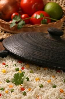 나무 테이블에 흰 접시에 야채와 함께 식욕을 돋 우는 건강 한 쌀. 쌀 색깔