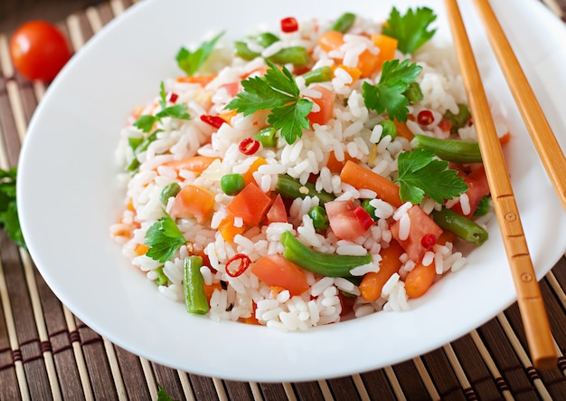 Аппетитный здоровый рис с овощами в белой плите на деревянном столе.
