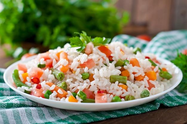 木製のテーブルの白い皿に野菜と食欲をそそる健康的な米。