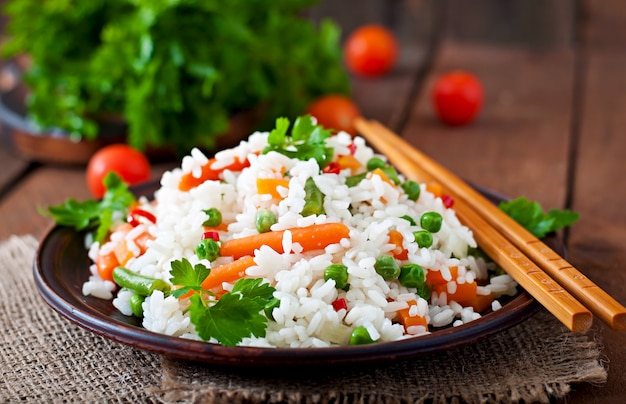 Appetizing healthy rice with vegetables in white plate on a wooden table.