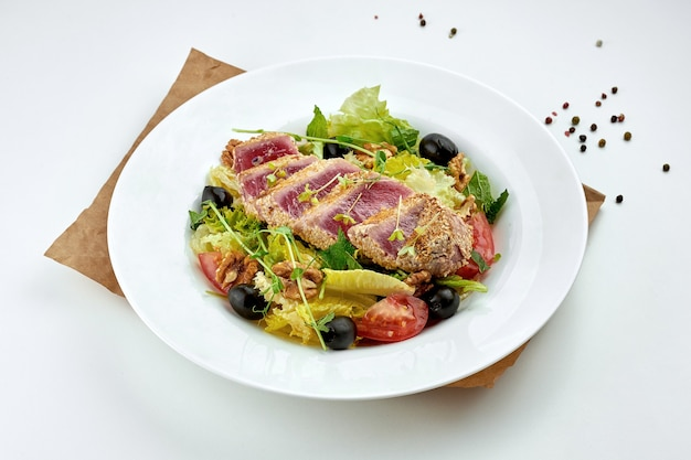 Appetizing and healthy salad with grilled tataki tuna steak, tomatoes and olives, served in a white plate. white surface