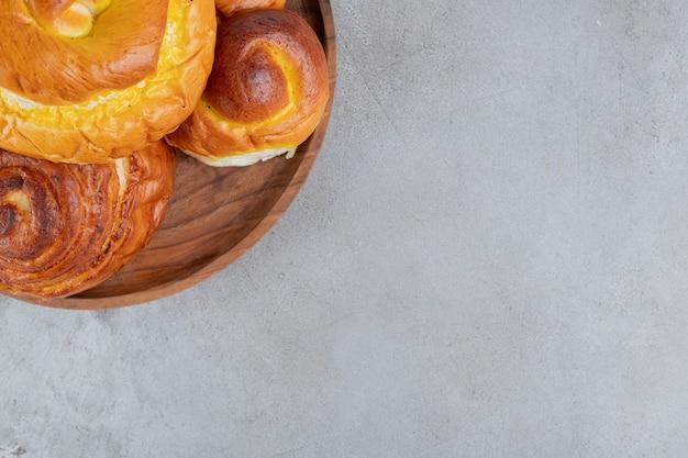 Аппетитная куча сладких булочек на маленьком подносе на мраморной поверхности