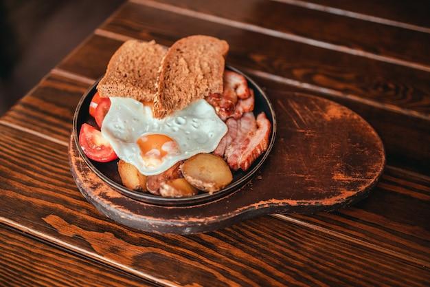 Аппетитный сытный завтрак с яйцом, беконом, помидорами и колбасой на тарелке в ресторане