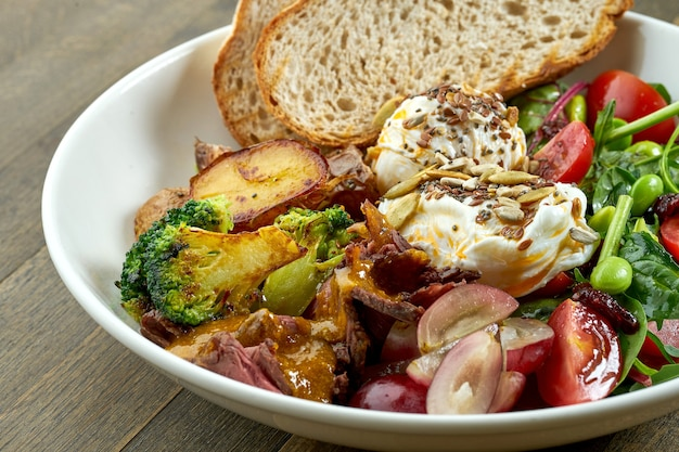 Appetizing and hearty breakfast with poached egg, potatoes, bacon, grapes, mix salad and rye bread in a white bowl on wooden table