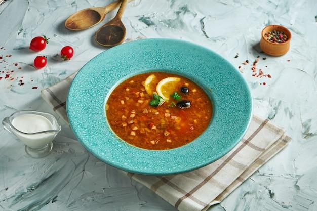 Аппетитная солянка на красном бульоне с колбасками и копченым мясом, маслинами и лимоной в белой тарелке на сером столе