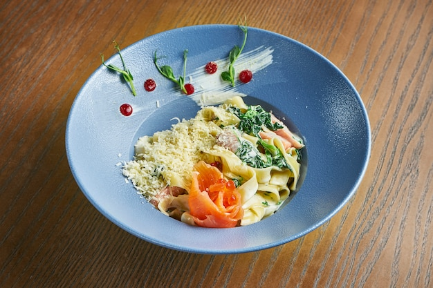 Appetizing, home-made tagliatelle pasta with spinach and salmon, parmesan in a blue bowl on a wooden surface. italian cuisine. add noise on post. selective focus