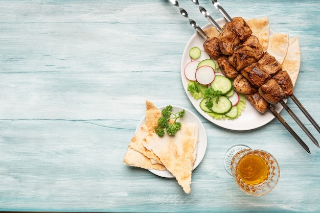 Appetizing homemade shish kebab, sliced vegetables, a glass of wine top view on a blue wooden background.