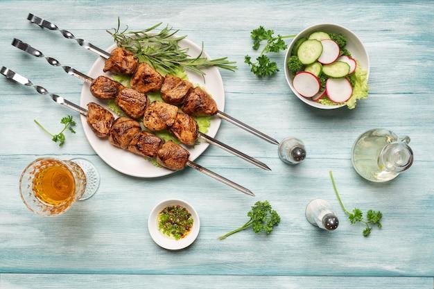 푸른 나무 배경에 있는 맛있는 홈메이드 시시 케밥 야채와 와인 한 잔