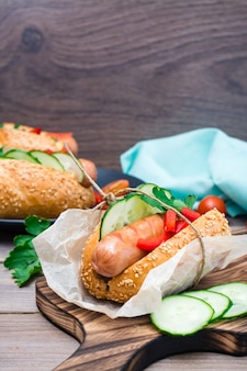 Appetizing hot dog made from fried sausage, rolls and fresh vegetables, wrapped in parchment paper on a cutting board on a wooden table