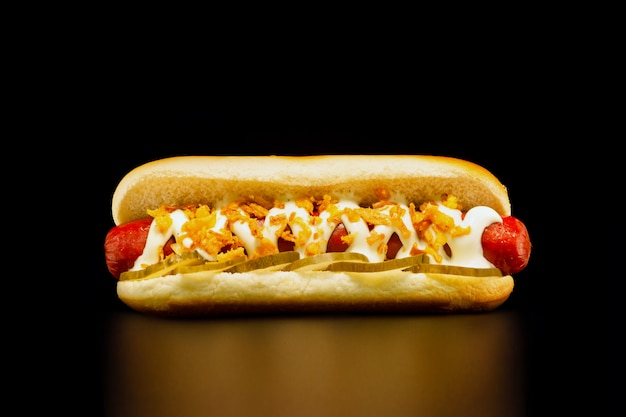 Appetizing hot dog with grilled beef sausage , pickles, mayonnaise and fried onions on black