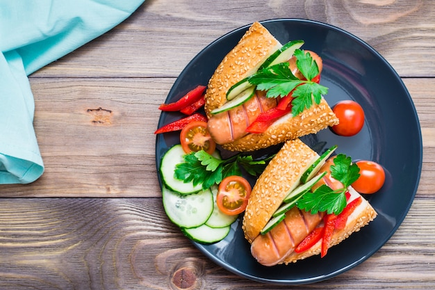Appetizing hot dogs from fried sausages, sesame buns and fresh vegetables on a plate on a wooden table