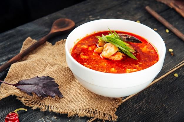 Аппетитный горячий красный суп том ям в белой миске