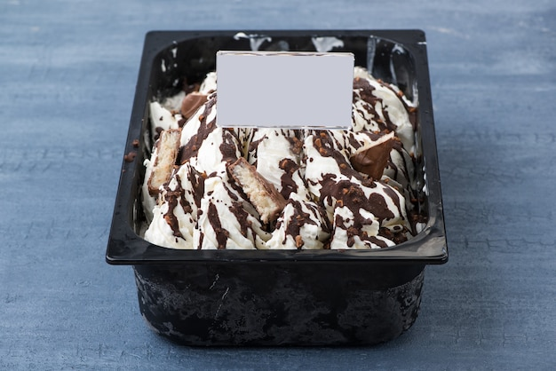 Аппетитное мороженое в пластиковой таре с ценником на декоративном синем фоне