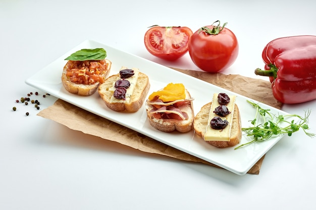 Appetizing italian antipasti - assorted bruschetta with salmon, cheese and jamon, served on a white plate on a white plate